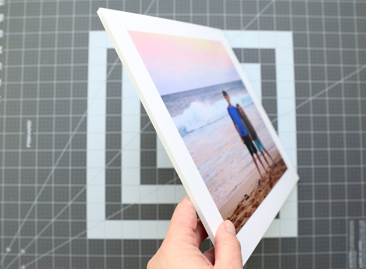 Photo adhered to a square of white foam core board