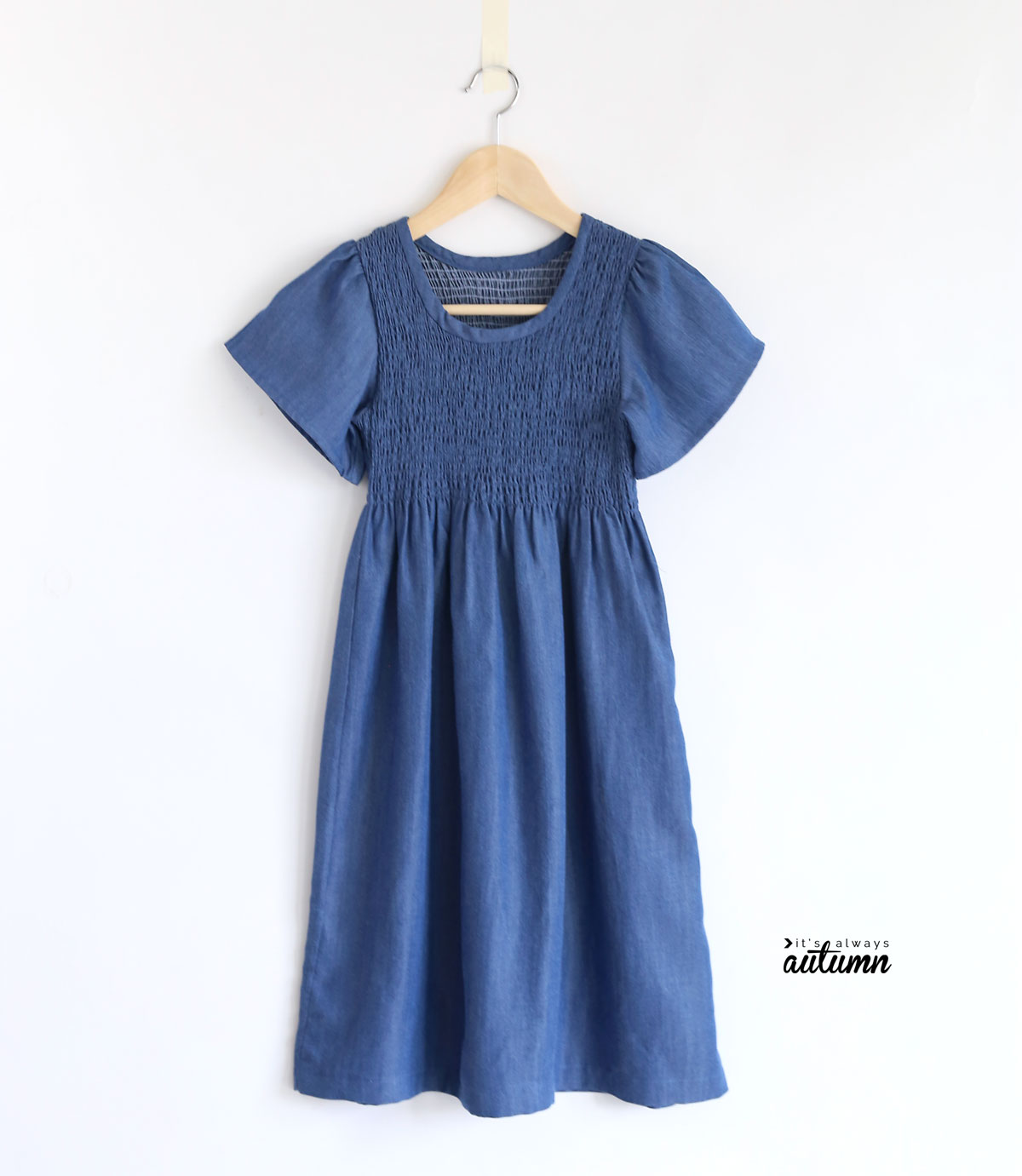 Blue dress with gathered bodice on a wood hanger