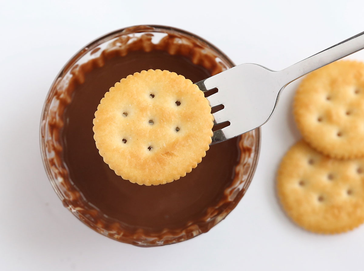 Fork holding Ritz cracker above bowl of melted thin mints