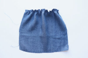 Square of blue chambray fabric that's been gathered across the top with one line of elastic thread