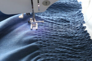 Piece of fabric smocked with elastic thread on a sewing machine