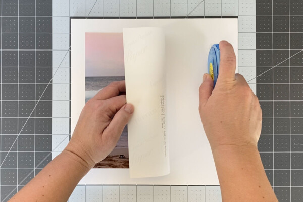 Square of white foam core with a photo centered on it, hand lifting the right half of the photo to put adhesive on the board
