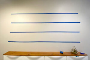 Wall in a hallway with blue painters tape marking four horizontal rows