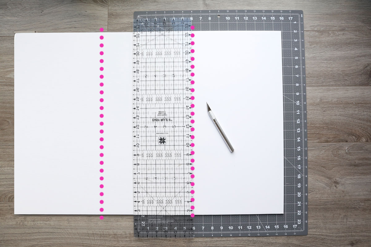 Foam core board on a large cutting mat with clear ruler and exacto knife; two dotted lines marking where board will be cut