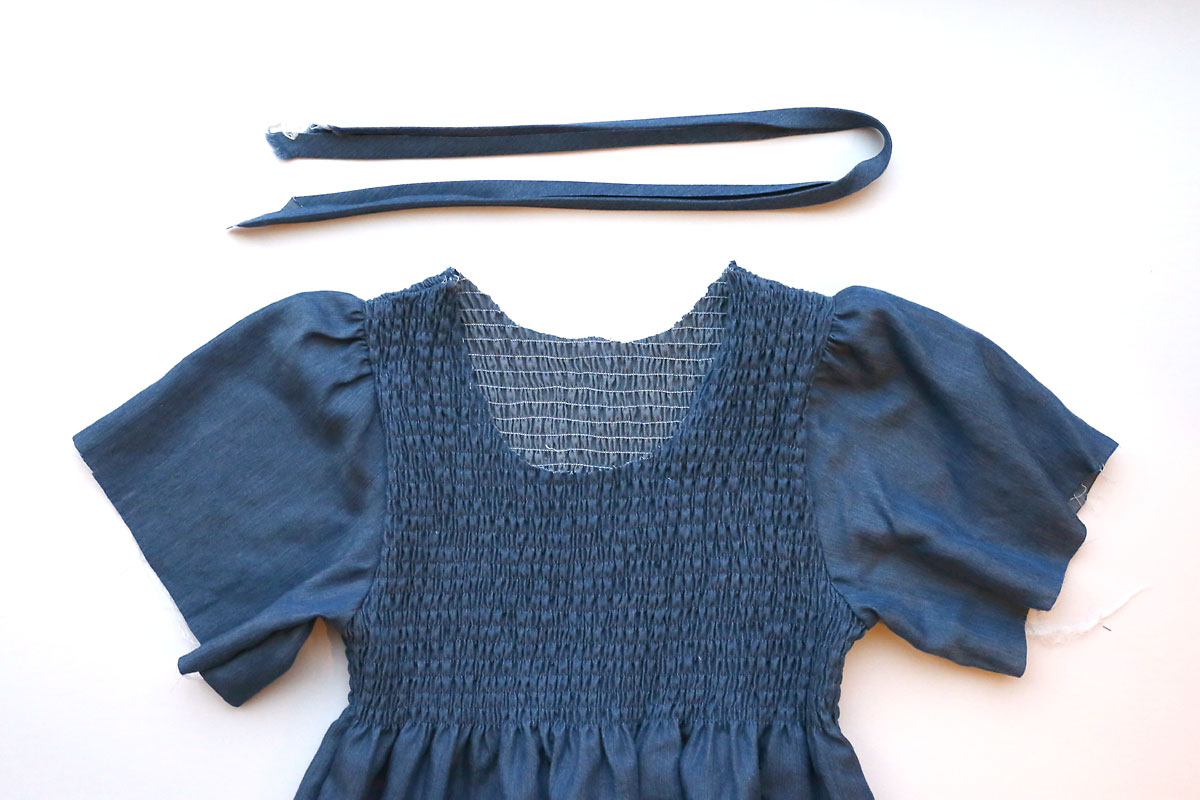 Top of chambray dress with neckline cut low enough to fit over head without stretching; bias tape made from same fabric