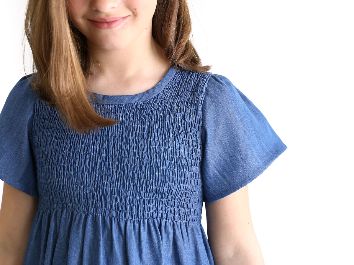 Closeup of the bodice and sleeve of a chambray dress with a smocked bodice