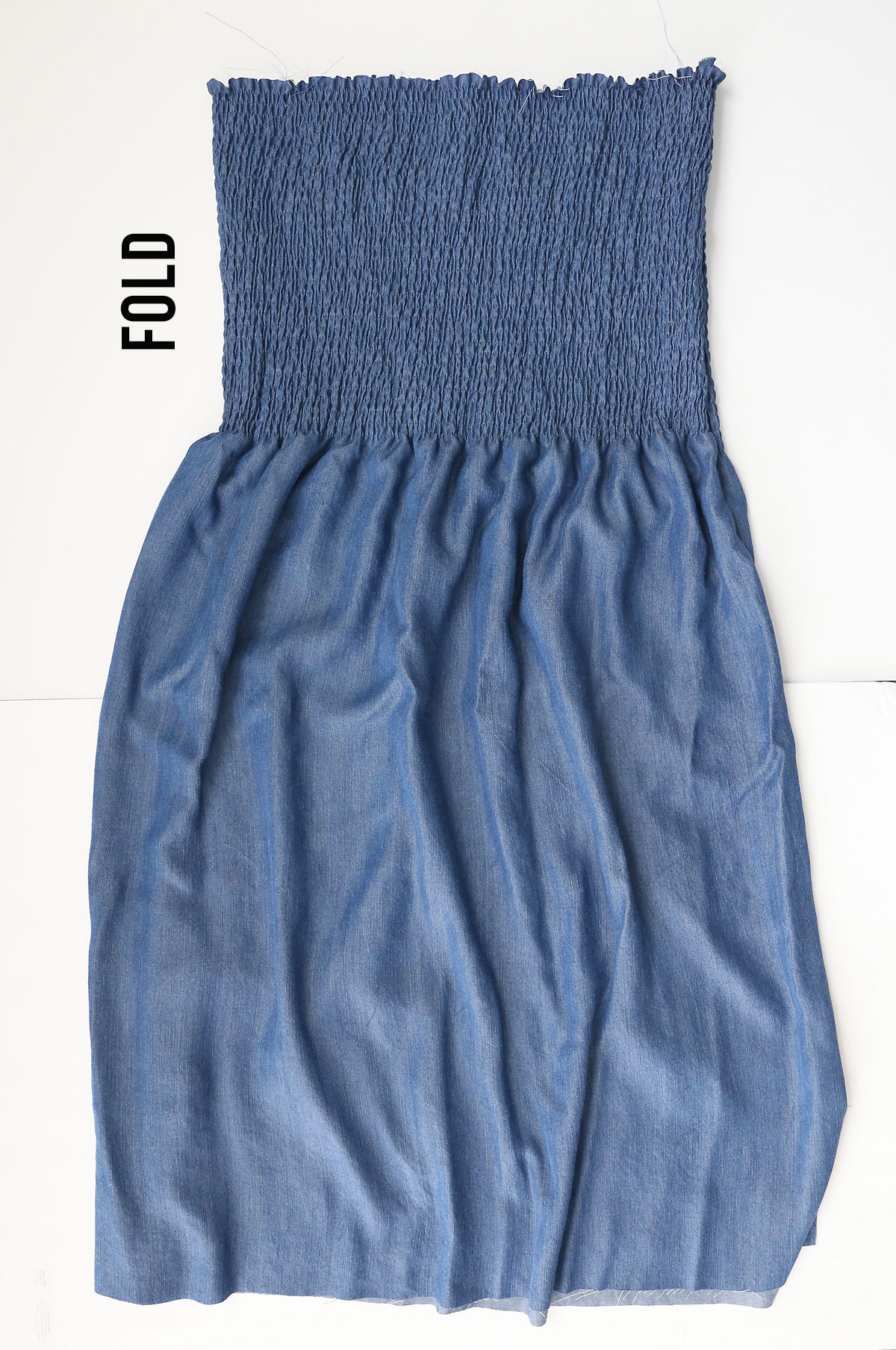 Chambray fabric that has been smocked with elastic thread along the top third, folded in half lengthwise