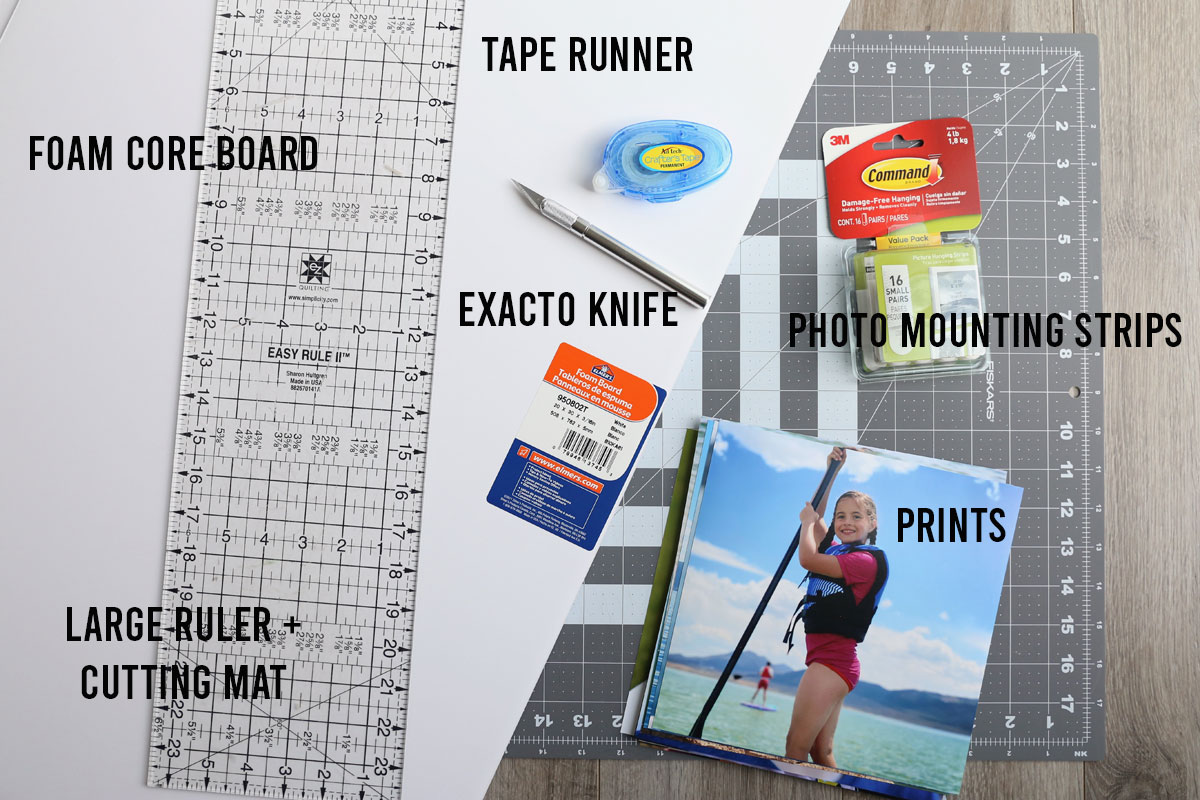 DIY gallery wall supplies: foam core board, photos, tape runner, exacto knife, Command photo strips, cutting board, large ruler
