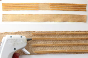 Two strips of burlap ribbon with four pipe cleaners laid on either side; hot glue gun to glue pipe cleaners to ribbon