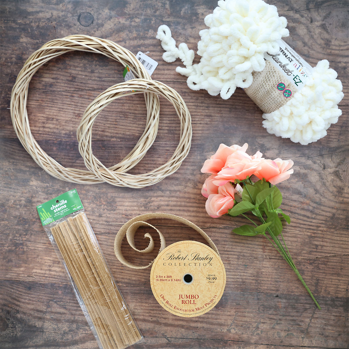 supplies: two wreath forms, cream loop yarn, faux flowers, burlap ribbon, pipe cleaners