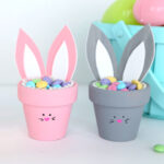 Two flower pot bunnies with Easter candy in front of an Easter basket