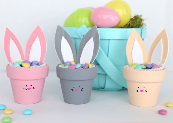 Three flower pot bunnies filled with Easter candy in front of an Easter basket