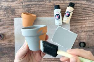 Hand holding foam brush painting small flower pot gray