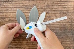 Hand gluing white foam inner ear to grey foam bunny ear