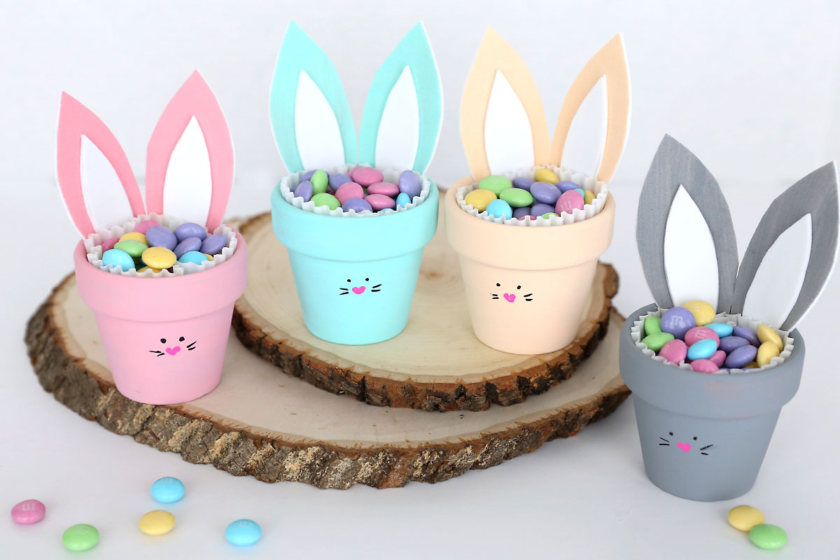 Four flower pot bunnies filled with candy, pink, turquoise, cream, and grey colored bunny pots