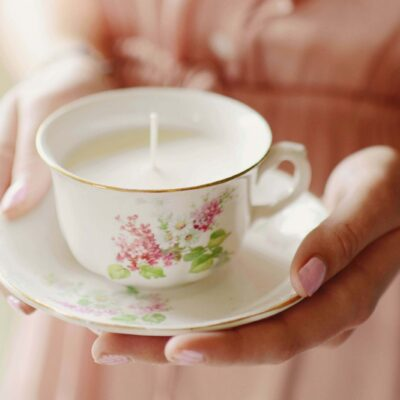 Hands holding teacup candle