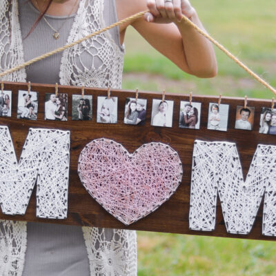 """Girl holding sign that says """"mom"""" and has photos on it"""