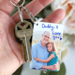 Hand holding keychain with picture of a little girl and her dad that says: Daddy I love you!