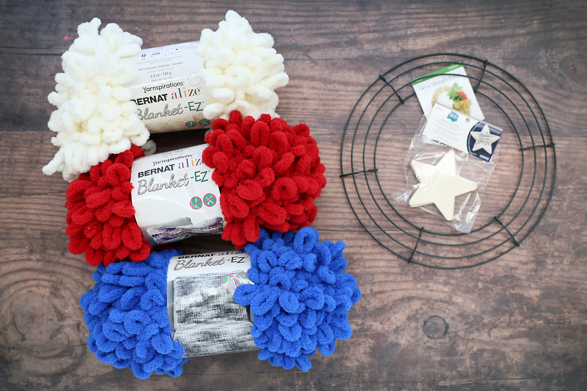 White, red, and blue loop yarn; wire wreath frame; wood star shapes