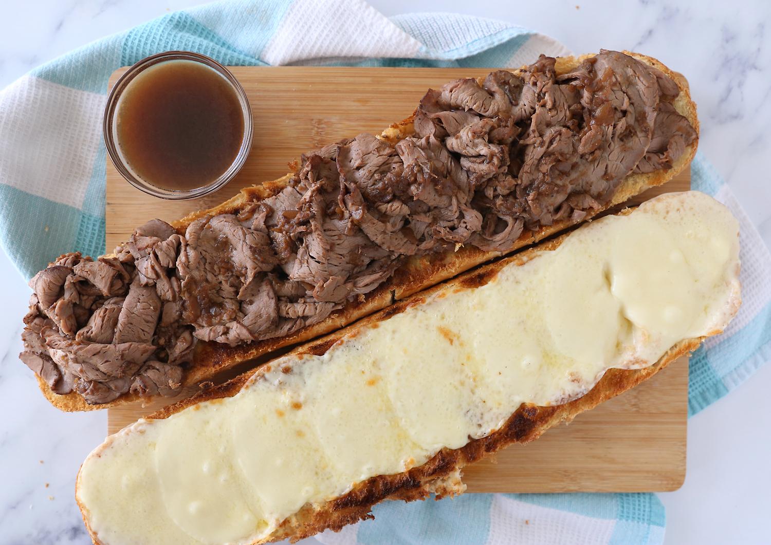 Open face french dip sandwich made on a loaf of french bread