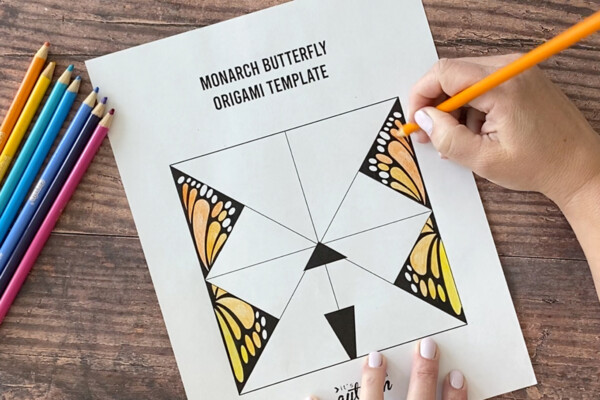 Hand coloring in a Monarch butterfly origami template with coloring pencils