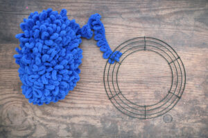 Blue loop yarn with one end tied to a wire wreath frame