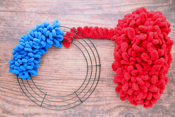 Wire wreath frame on quarter covered with blue loop yarn; a ball of red loop yarn tied to the frame