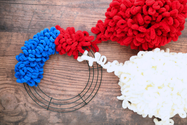 Wire wreath frame wrapped with blue and red loop yarn; white loop yarn tied on