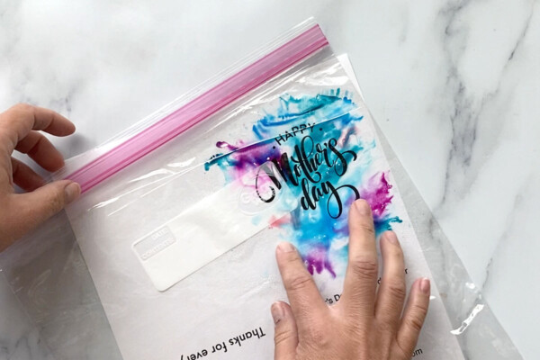 Bag with ink has been flipped over onto the paper, hand is blending the colors