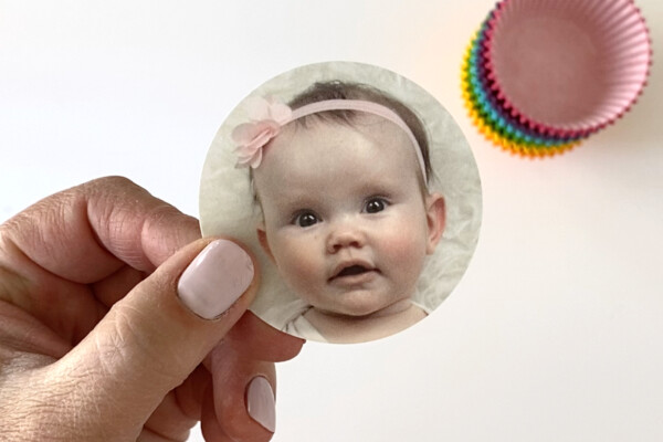 Hand holding photo of a baby cut into a circle