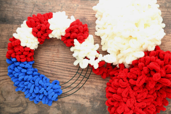 Wire wreath frame wrapped with blue loop yarn on one quarter; also wrapped with red and white loop yarn in stripes