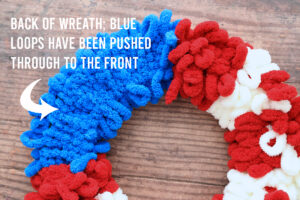 Back of loop yarn wreath with words: back of wreath; blue loop yarn have been pushed through to the front
