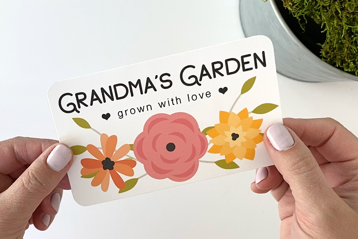 Hands holding a label with words: Grandma's Garden, grown with love; and flowers