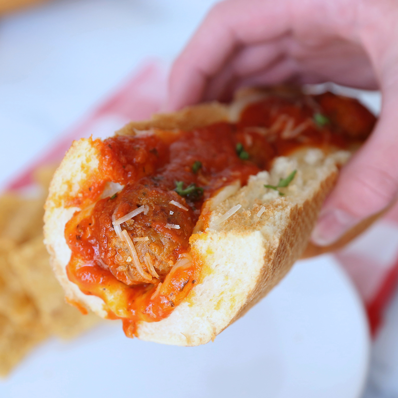 Hand holding a meatball sandwich