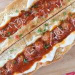 Two large meatball sandwiches on a cutting board