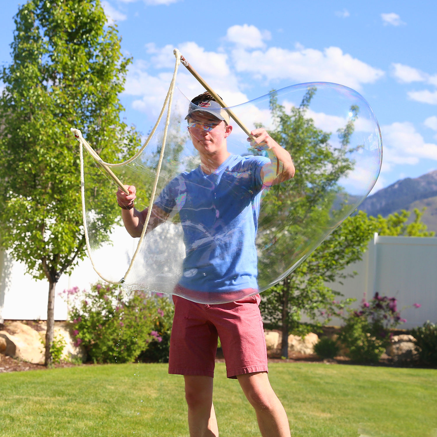 Boy holding giant bubble wand to blow giant bubbles