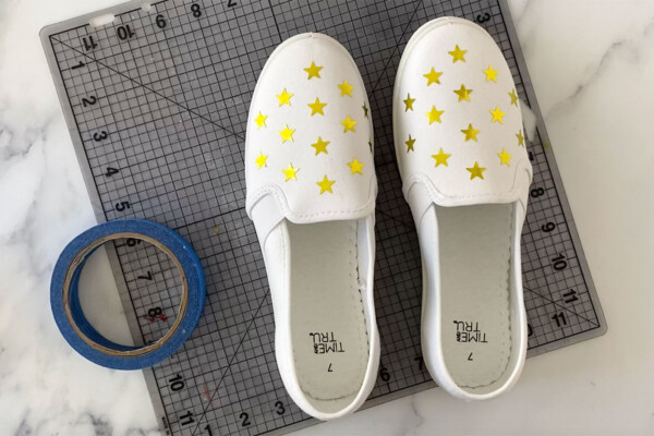 Canvas shoes with star stickers on the tops; roll of tape
