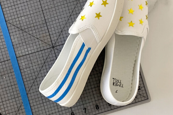 Pair of white canvas shoes with star stickers on the top and rows of masking tape along the back