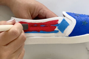 Painting red stripes on a canvas shoe
