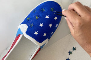Removing star stickers from top of painted shoe with tweezers