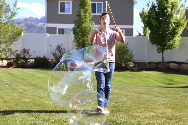 Boy holding DIY bubble wand with sticks back together to close off bubble