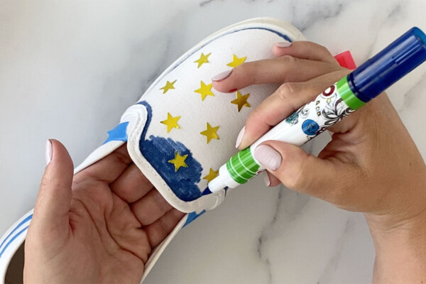 Canvas shoe with star stickers on it; hand coloring it with blue fabric marker