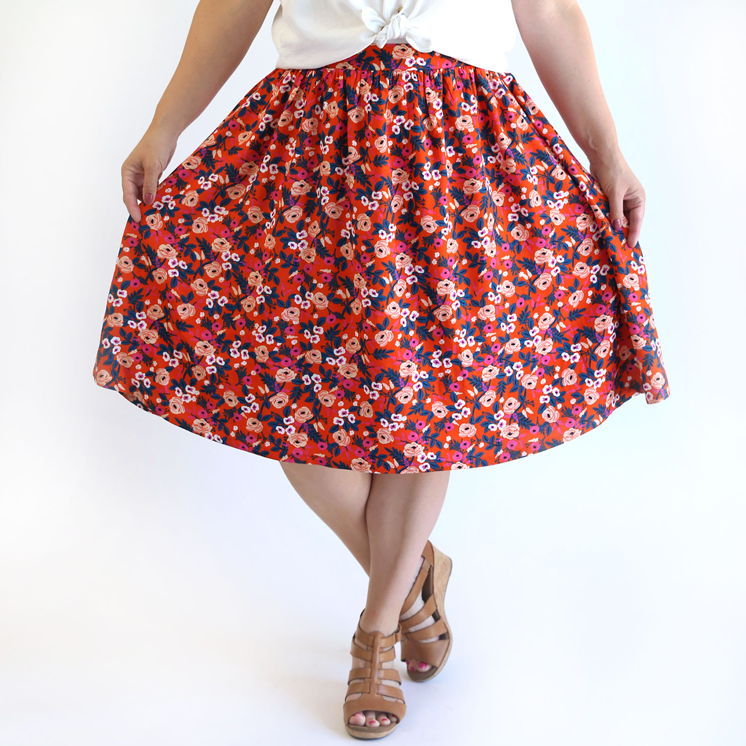 Woman wearing red floral skirt with flat front waistband and gathered back waistband