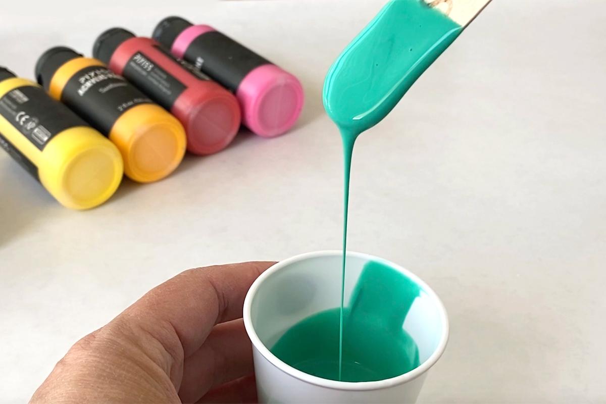 Palito de paleta recogiendo pintura de una taza pequeña;  la pintura vuelve fácilmente a la taza