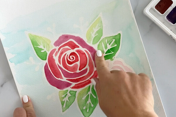 Using fingers to rub the rubber cement outline off the floral painting