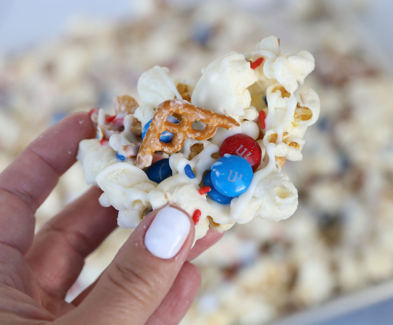 Hand holding white chocolate popcorn snack mix