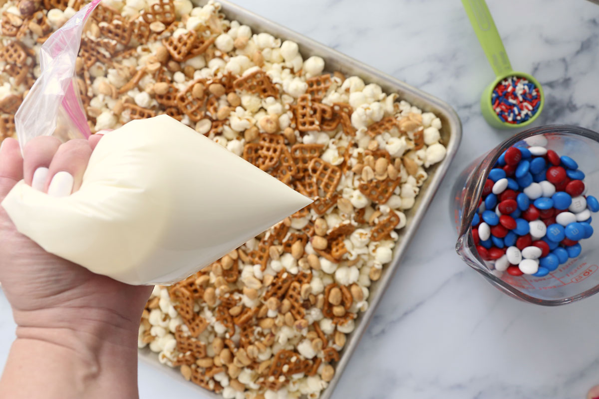 White chocolate melted in a ziplock bag to pipe over popcorn, pretzels and peanuts
