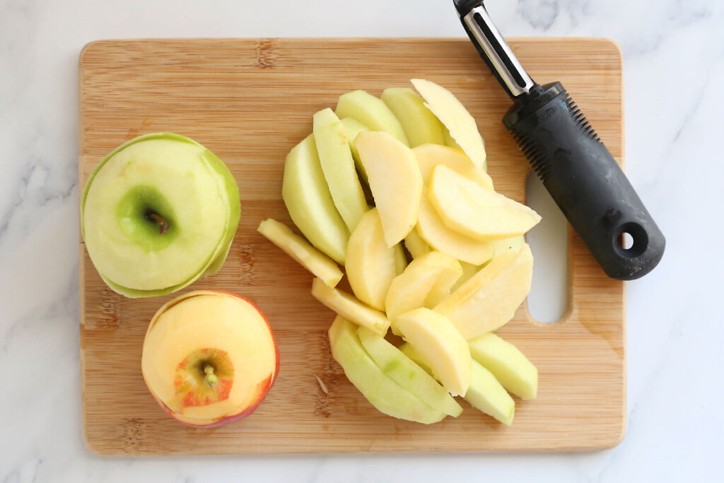 Peeled and sliced apples on a cutting board with peeler