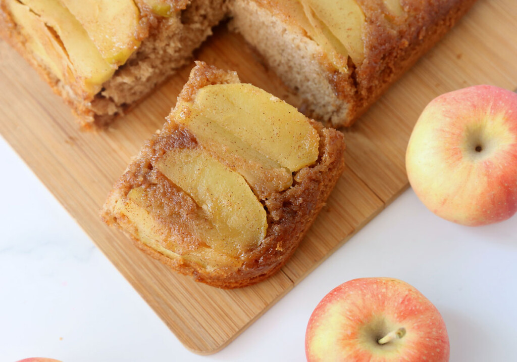 Sliced of apple upside down cake on a cutting board; apples
