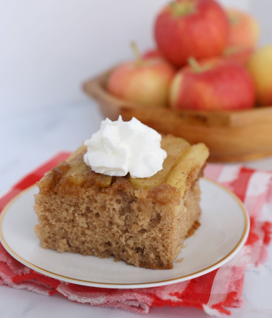 Piece of apple upside down cake on a plate with whipped cream